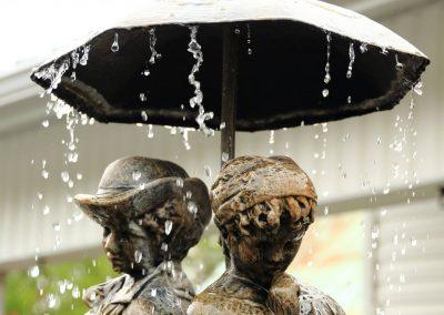 fontaine d'eau en pierre avec parapluie