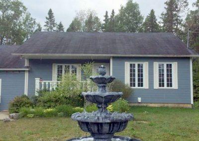 Fontaine devant une maison bleue
