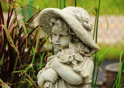 Sculpture d'enfant avec fleurs et chapeau