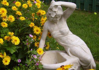 Statue de femme avec fleurs jaunes